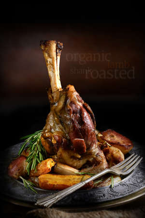 Roast lamb shank with roasted potatoes and carrots styled in a rustic setting with generous copy space. Concept image for home cooking or your bistro or restaurant menu cover design.