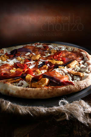 pizza base: A stone baked wood fired pizza base topped with a tomato and herb sauce, mozzarella, chorizo, paprika seasoned chicken, Cherry Bell tomatoes, Peppers and balsamic red onion finished with parsley. Stock Photo