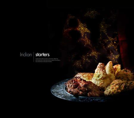 Creatief verlicht schotel van traditionele Indiase gerechten voorgerechten en hapjes tegen een sprankelende Indische achtergrond met accommodatie voor kopie ruimte. Stockfoto