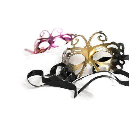 masquerade masks: Masquerade carnival masks against a white background. Concept image for traditional New Years Eve party with ribbon and accommodation for copy space. Stock Photo