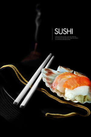 Fresh Japanese sushi with chop sticks, burning incense and luxury napkin against a black background. Generous accommodation for copy space.