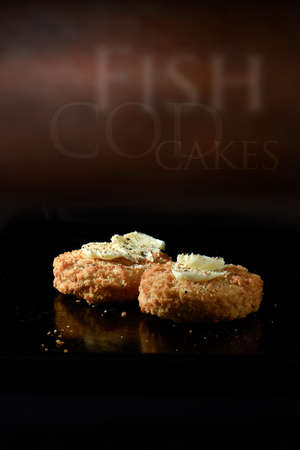 accommodation space: Creatively lit fresh cod fillet fish cakes with seasoning and butter prior to cooking against a rustic background. Generous accommodation for copy space. Stock Photo