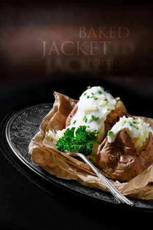 Creatively lit meal setting of two baked jacket potatoes with grated cheddar cheese, soured cream and chives in a rustic environment with generous accommodation for copy space.