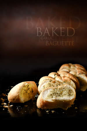 lit image: Creatively lit close up image of fresh crusty garlic bread baguette with butter and herbs against a rustic background setting. Generous accommodation for copy space. Stock Photo