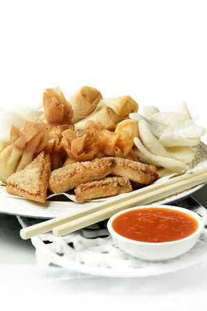 accommodation space: Chinese selection of tasty appetizers, crispy dum sum chicken wontons, vegetable spring rolls and prawn toast against a light background. Accommodation for copy space. Stock Photo