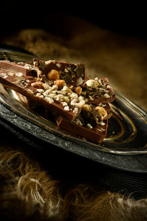 lit image: Creatively lit image of broken pieces of rocky road chocolate on an antique pewter serving plate against a dark, rustic background. Accommodation for copy space.