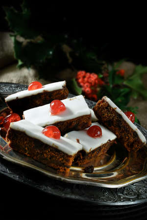 accommodation space: Creatively lit festive iced fruit cake slices with glace cherries, sultanas, currants and raisins soaked in French brandy with thick white fondant icing. Accommodation for copy space. Stock Photo