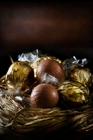 accommodation space: Creatively lit Swiss milk chocolate truffles in a nest of gold against a rustic background with generous accommodation for copy space. Concept image for your dessert or valentines menu. Stock Photo
