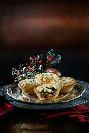 minced pie: Thanksgiving or Christmas festive lattice pastry mince pies on antique pewter plate against a rustic background with accommodation for copy space.