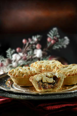 Thanksgiving or Christmas festive lattice pastry mince pies on antique pewter plate against a rustic background with accommodation for copy space.