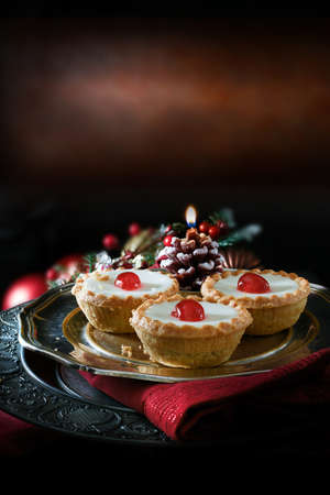 pewter: Thanksgiving or Christmas festive iced pastry mince pies on antique pewter plate against a rustic background with accommodation for copy space.