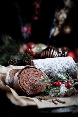 roulade: Festive chocolate Yule log in Christmas setting with generous accommodation for copy space. Concept image for your Thanksgiving or Christmas dessert menu designs.
