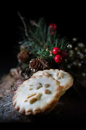mulled: Creatively lit, festive Christmas or Thanksgiving mince pies against a dark background in a rustic setting.