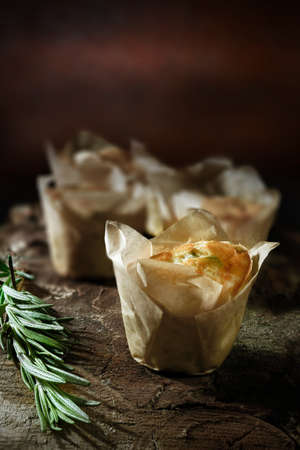 accommodation space: Italian cheese and onion mini souflettes with rosemary herb against a rustic dark background. Generous accommodation for copy space. Stock Photo