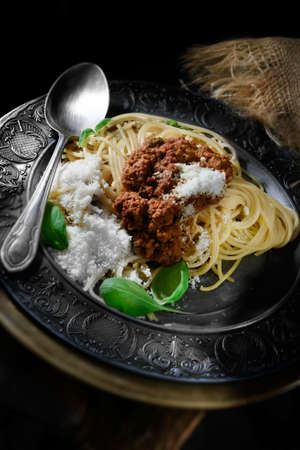 creatively: Creatively lit Italian spaghetti bolognese with basil herbs and grated parmesan cheese against a rustic background with selective focus. Cover image for Italian cuisine. Copy space. Stock Photo