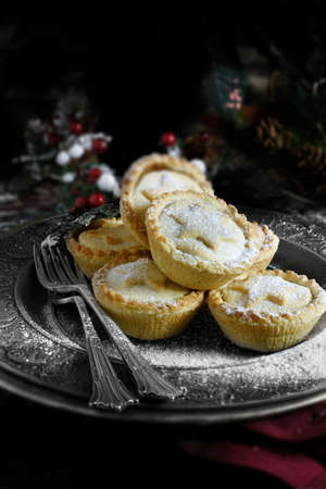 Sugar frosted festive mince pies in a rustic setting with a dark background. Accommodation for copy space. The perfect cover image for your Christmas or Thanksgiving dessert menu design. Stok Fotoğraf