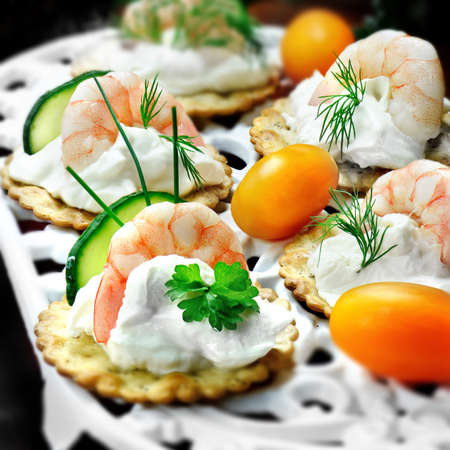 garnish: Festive fresh prawn and soft cheese canapes with cucumber and tomato relish and dill and parsley garnish. Square crop. Differential focus.