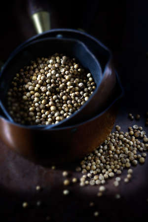 differential focus: Creatively lit cilantro seeds also known as coriander, in Indian copper pans against a rustic background. Concept image for Indian cooking. Differential focus.