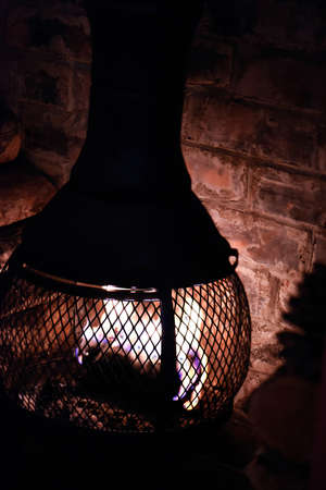 cosy: Traditional old fashioned wood burner chimney burner in very old brick open fireplace. Concept image for cosy nights in, fire side warmth and winter warmers. Copy space.