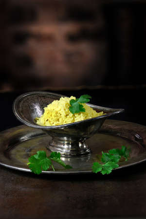 lit image: Creatively lit image of steamed Indian Pilau Rice in an antique serving dish against a rustic, dark background. Perfect image for your Indian restaurant menu design with generous copy space.