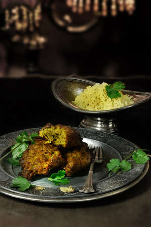 accommodation space: Creatively lit Indian Onion Bhajis with pilau rice against a dark, rustic styled background. The perfect image for your indian menu cover design. Generous accommodation for copy space. Stock Photo