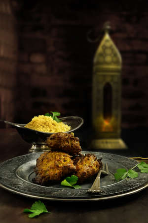 plato de comida: Creativa iluminado Bhajis cebolla indias con arroz pilaf contra un oscuro aut�nticamente indio, fondo de estilo r�stico. La imagen perfecta para su dise�o de la cubierta del men� indio. alojamiento generosa para copiar el espacio. Foto de archivo