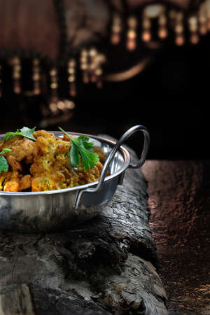 lit image: Creatively lit Indian Onion Bhajis against a dark, rustic styled background. The perfect image for your indian menu cover design. Generous accommodation for copy space.