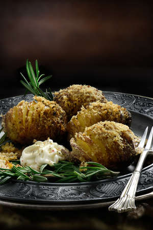 creatively: Creatively lit Swedish styled Hasselback potatoes with crusted breadcrumbs and parmesan cheese coating with rosemary herbs and garlic mayonnaise dip  against a rustic background. Copy space. Stock Photo