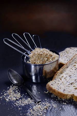 Freshly milled granary loaf breadcrumbs in steel measuring cups against a  rustic background. Concept image for cooking or food preparation. Generous accommodation for copy space. Stock Photo