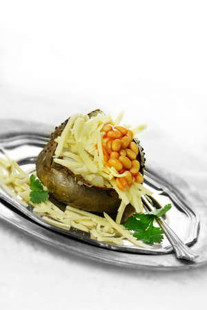 accommodation space: Baked jacket potato with grated cheese and baked beans with garnish against a white background. Generous accommodation for copy space. Stock Photo