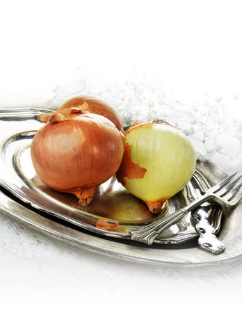 pewter: British brown onions set on a antique pewter plate against a light, bright background. Generous accommodation for copy space.