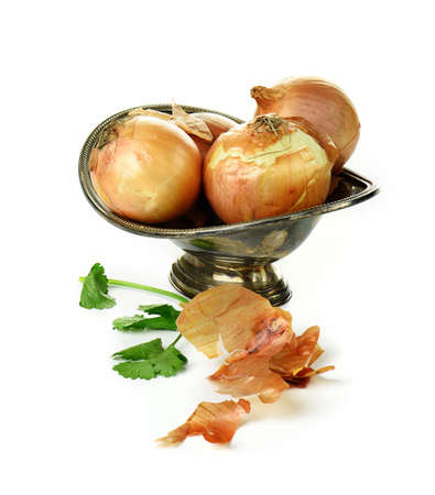 pewter: British brown onions set in a antique pewter bowl against a light, bright background. Generous accommodation for copy space.