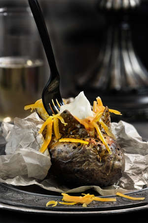 accommodation space: Baked jacket potato with red grated cheese against a dark background. Generous accommodation for copy space. The perfect image for your lunch menu cover design. Stock Photo