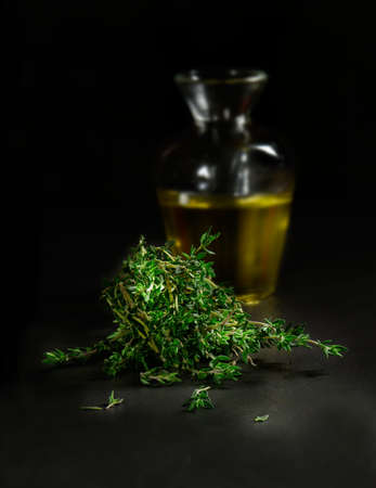 ingedient: Creatively lit studio image of fresh thyme herb leaves against a dark background with a decanted glass flask of olive oil. Concept image for Italian cooking ingredients. Copy space.