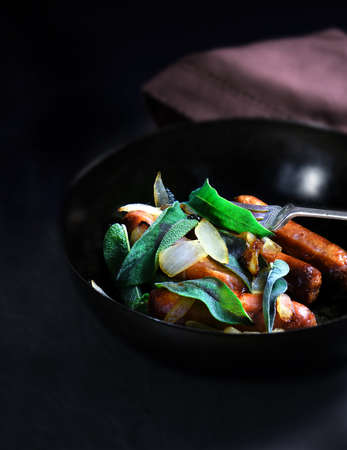 accommodation space: Creatively lit cuisine dish of sausage and onions with sage herbs against a dark background with generous accommodation for copy space.