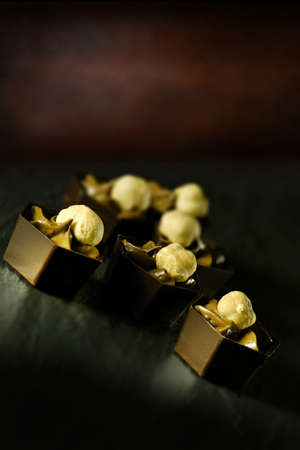 accommodation space: Luxury hazelnut and praline liqueur mousse chocolates on a dark surface against a rustic background. Generous accommodation for copy space.