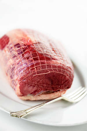 roast: An image of uncooked prime topside roast beef against a light background with copy space. Concept image for a restaurant Sunday lunch menu cover design or cooking instructions.