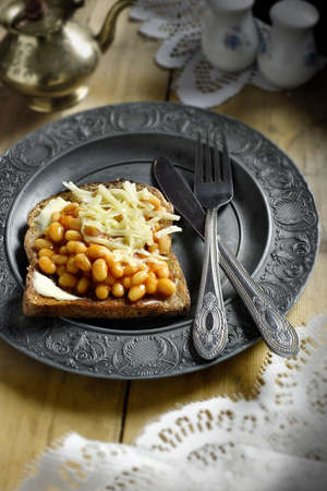 queso rallado: frijoles al horno y queso rallado sobre pan tostado con mantequilla con un enfoque selectivo y la iluminación creativa. Espacio de la copia. Foto de archivo