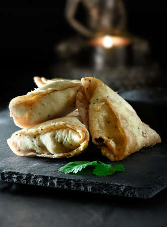 Creatively lit close up image of Indian vegetable samosas appetizers with coriander garnish on slate against a dark background. Generous accommodation for copyspace.