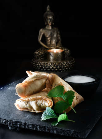 creatively: Creatively lit close up image of Indian vegetable samosas appetizers with coriander garnish on slate against a dark background. Generous accommodation for copy space.
