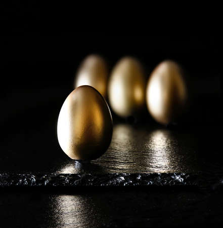 oiled: Creatively lit and positioned golden eggs against a black background on oiled slate. Concept image for investments, savings and pensions. Generous accommodation for copy space.