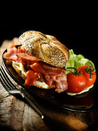 accommodation space: Glorious smoked bacon rashers in a sunflower seeded Viennese or Kaiser roll with lettuce and tomatoes. A different setup of an image for the classic BLT. Generous accommodation for copy space. Perfect for your lunch menu cover design. Stock Photo