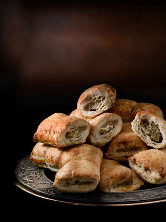 accommodation space: Mini cocktail sausage rolls stacked on a pewter plate against a dark rustic background. Generous accommodation for copy space.