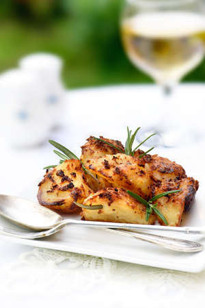 accommodation space: Freshly roasted potatoes with rosemary herbs in a summer setting with selective focus and generous accommodation for copy space. Stock Photo