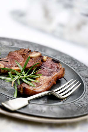 accommodation space: Close up image of two grilled lamb cutlets with rosemary herbs shot in natural light with daylight calibrated fill lights. Selective focus and genreous accommodation for copy space.