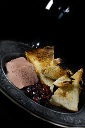 melba: Creatively lit slices of Brussels pate with melba toast and pickled cherries. Concept image for a dining or restaurant menu cover design. Generous accommodation for copy space.