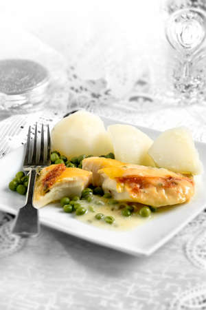 haddock: Fresh smoked haddock with par boiled potatoes and garden peas against a white background. Concept image for a wedding breakfast or reception. The perfect image for your restaurant menu cover design. Stock Photo