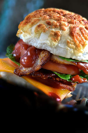 The classic Bacon, lettuce and tomato bun with the added twist of a Red Leicester slice of cheese. Creative lighting, selective focus and copy space. perfect for your bistro or cafe menu cover design. Stock Photo