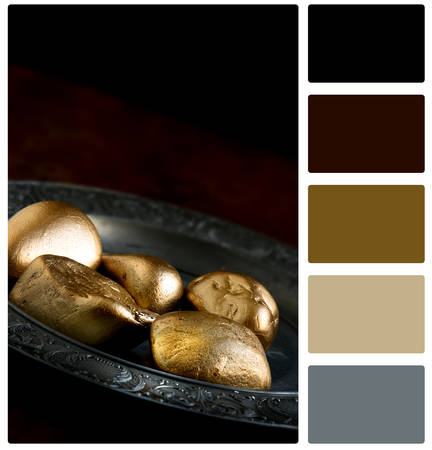 gold colour: Pension concept image with gold rocks opposed to golden eggs on an antique pewter plate. Image for pension danger, disappointment and low financial performance. Copy space and colour swatch palette. Stock Photo