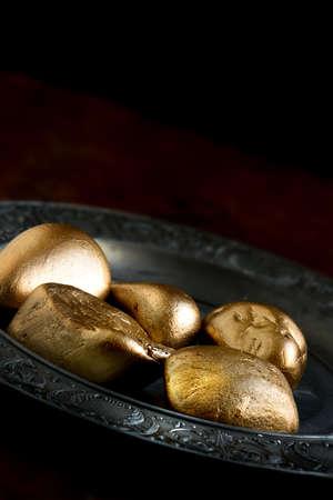 decepci�n: concepto de imagen de pensiones con las rocas de oro que se oponen a los huevos de oro en una placa de peltre antiguo. Imagen para el peligro de pensiones, la decepci�n y el bajo rendimiento financiero. Espacio de la copia.